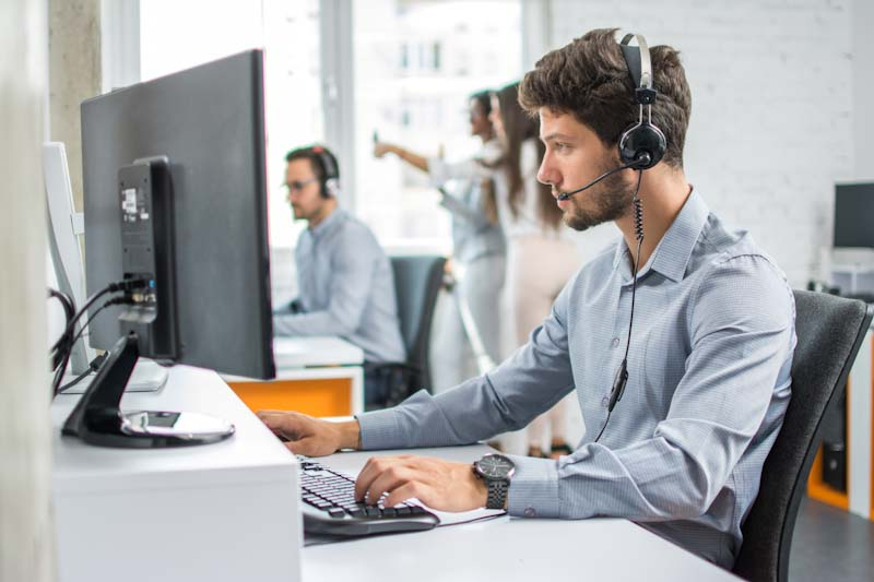 Photo of a man and a man providing IT assistance over a headset phone